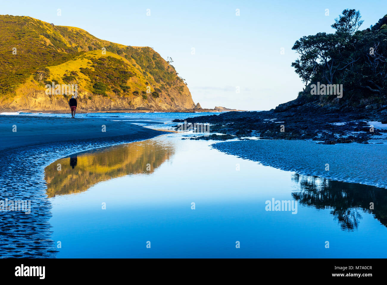 Man walking on beach where Tapotupotu Stream enters Tapotupotu Bay, near Cape Reinga, North Island, New Zealand Stock Photo