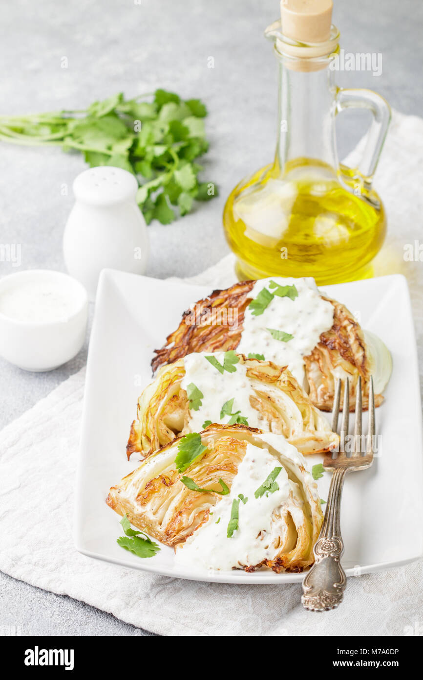 Baked pieces of cabbage with spices and yoghurt sauce, mustard and herbs. Selective focus - Stock Image