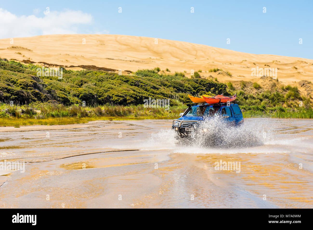 4x4 vehicle drives up the Te Paki Stream, used as a 'road' to access Ninety Mile Beach, North Island, New - Stock Image