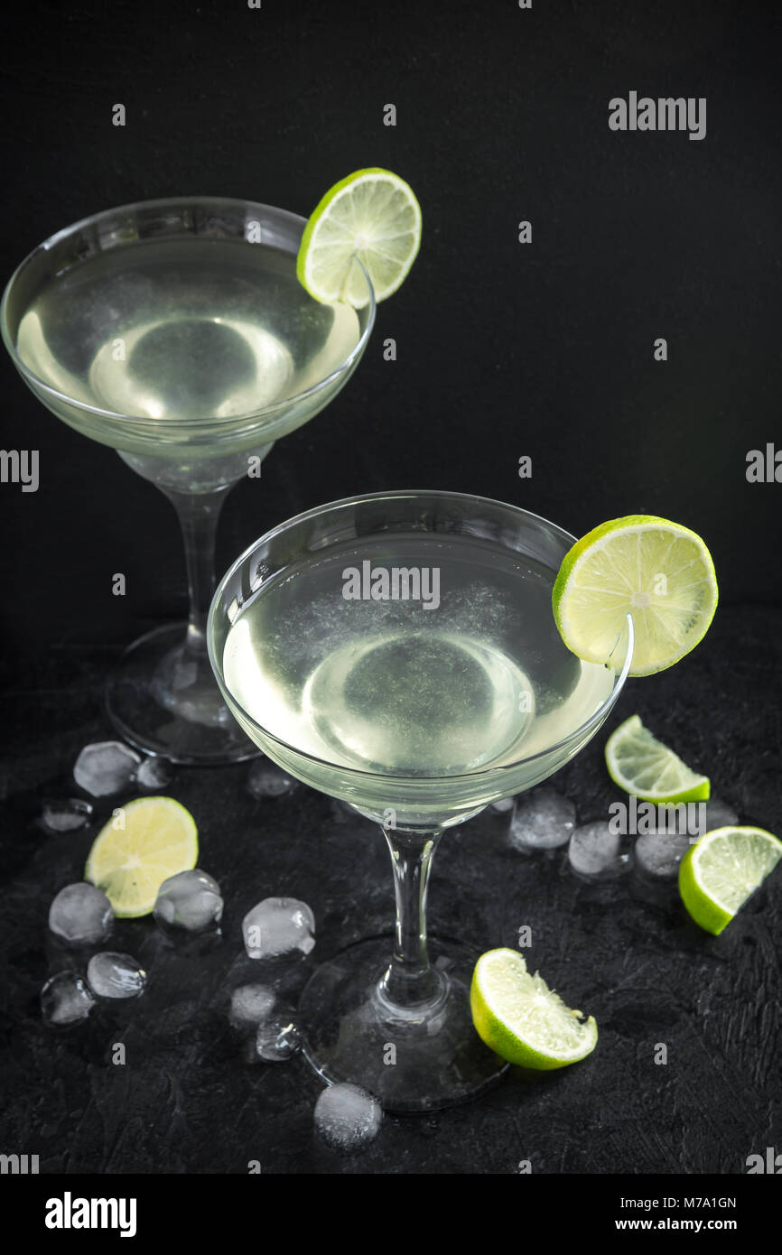 Margarita Сocktail with lime and ice on black stone table, copy space. Classic Margarita Cocktail. - Stock Image