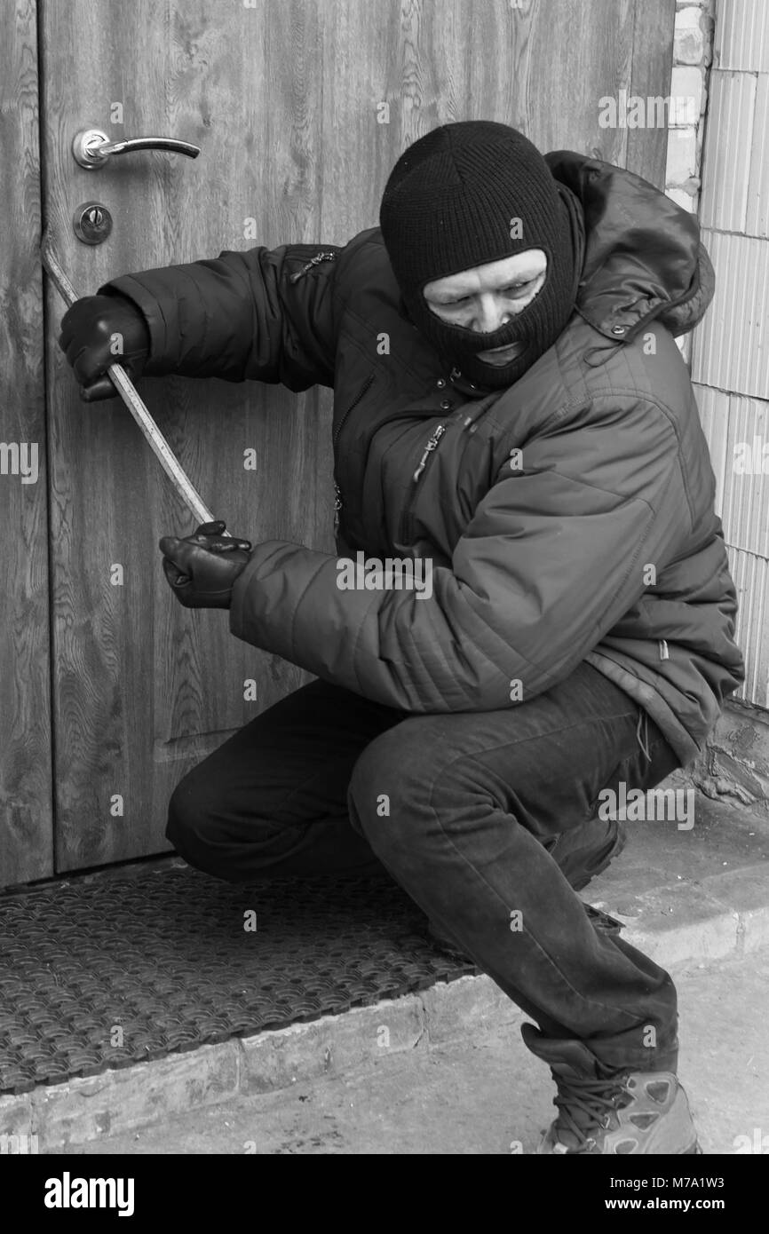 criminal breaks the door with crowbar. illegal entry into the home - Stock Image