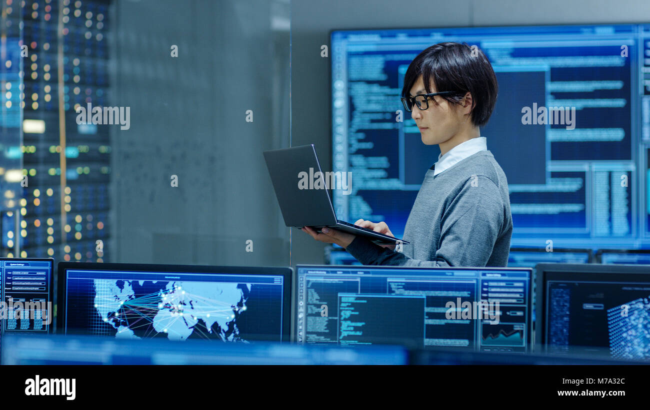 In the System Control Room IT Technician Works on a Laptop, in Background Multiple Displays with Graphics. Facility - Stock Image