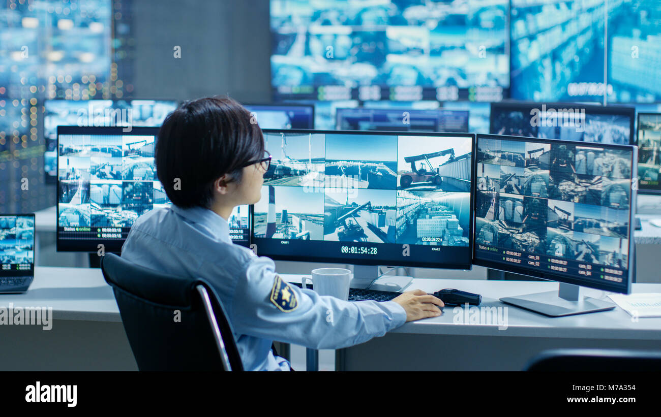 In the Security Control Room Officer Monitors Multiple Screens for Suspicious Activities, He Drinks from a Mug. - Stock Image