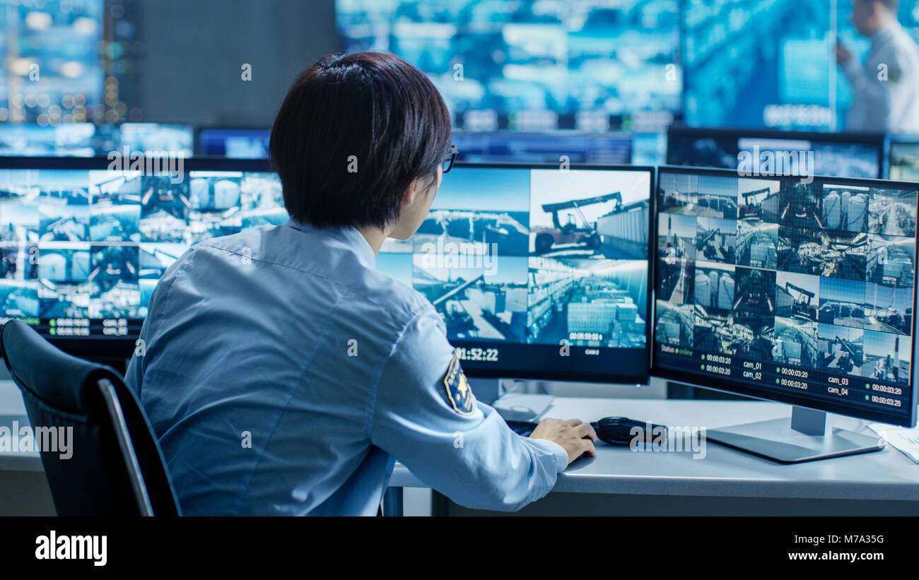 In the Security Control Room Officer Monitors Multiple Screens for Suspicious Activities. He's Surrounded by - Stock Image