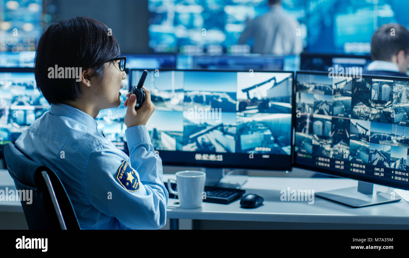 In the Security Control Room Officer Monitors Multiple Screens for Suspicious Activities, He Reports any Unauthorised - Stock Image