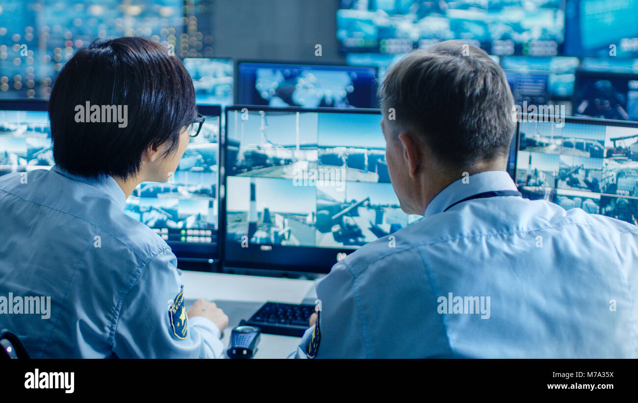 In the Security Control Room Two Officers Monitoring Multiple Screens for Suspicious Activitiee They Report Unauthorised - Stock Image