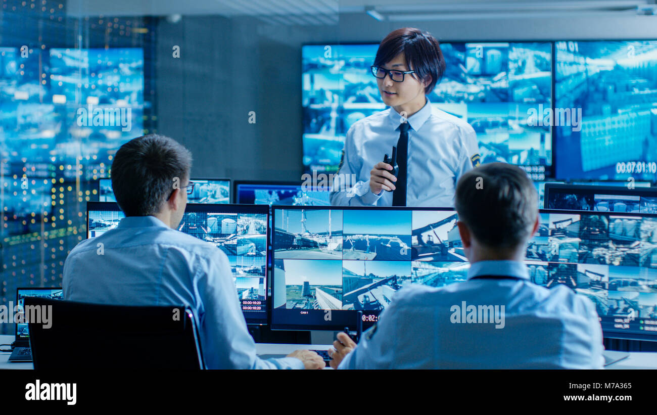 In the Security Control Room Chief Surveillance Officer Briefs Two of His Subordinates. Multiple Screens Show that - Stock Image