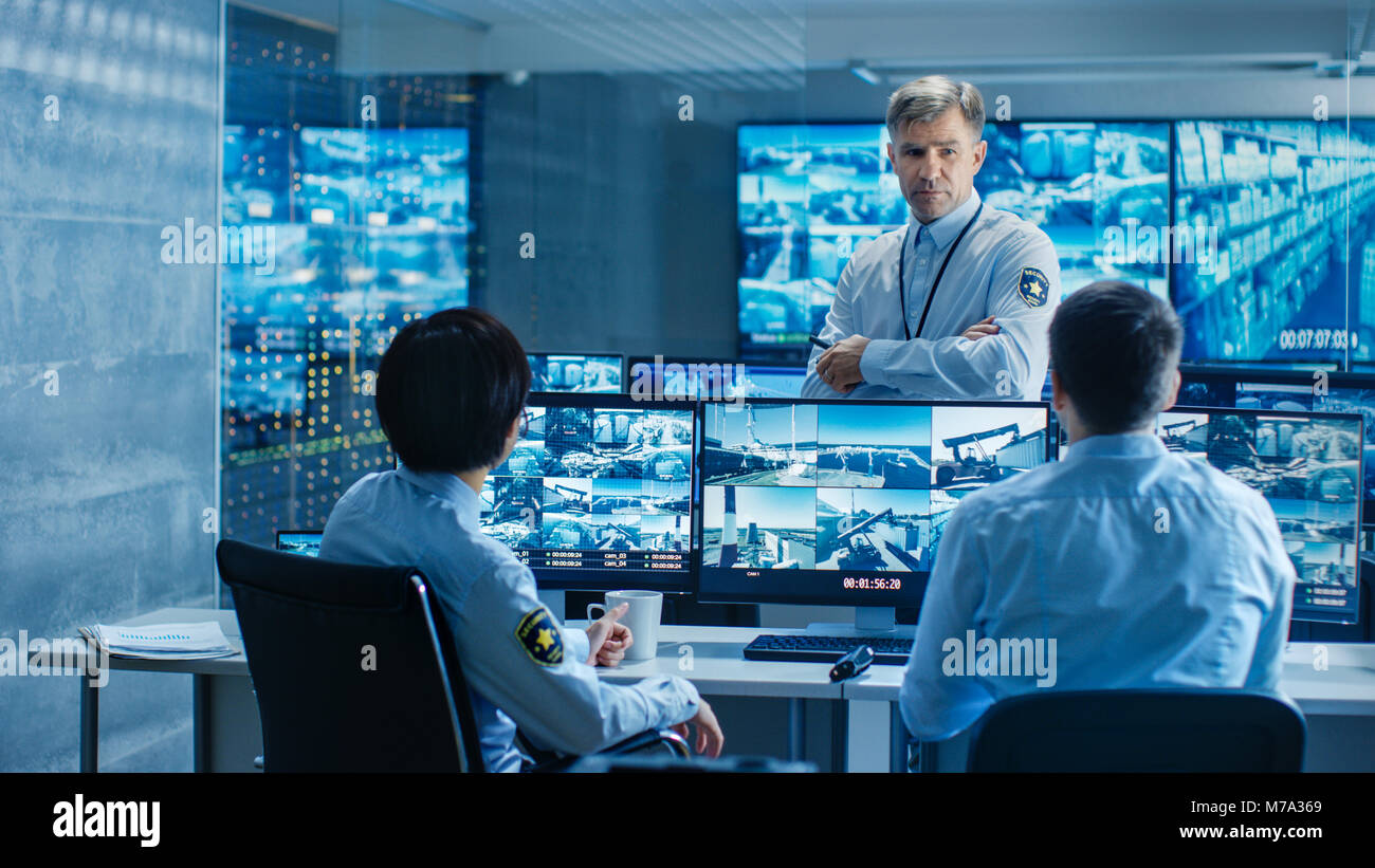 In the Security Control Room Chief Surveillance Officer Holds a Briefing for Two of His Subordinates. Multiple Screens - Stock Image