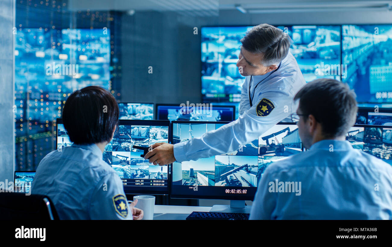 In the Security Control Room Chief Surveillance Officer Showing on Screen a Crime for Two of His Subordinates. Multiple - Stock Image