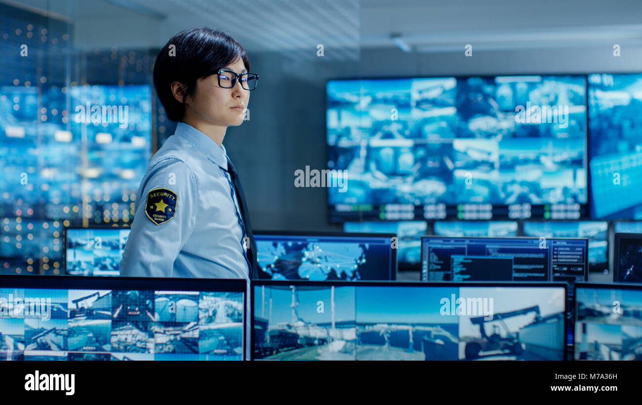 In the Security Control Room Officer Monitors Multiple Screens for Suspicious Activities. He Guards Internationally - Stock Image