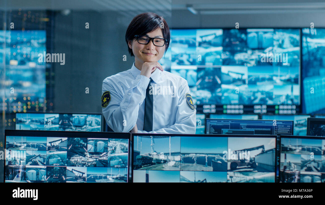 In the Security Room Officer Monitors Screens for any Suspicious Activities, He Smiles Into Camera. Screens Show - Stock Image