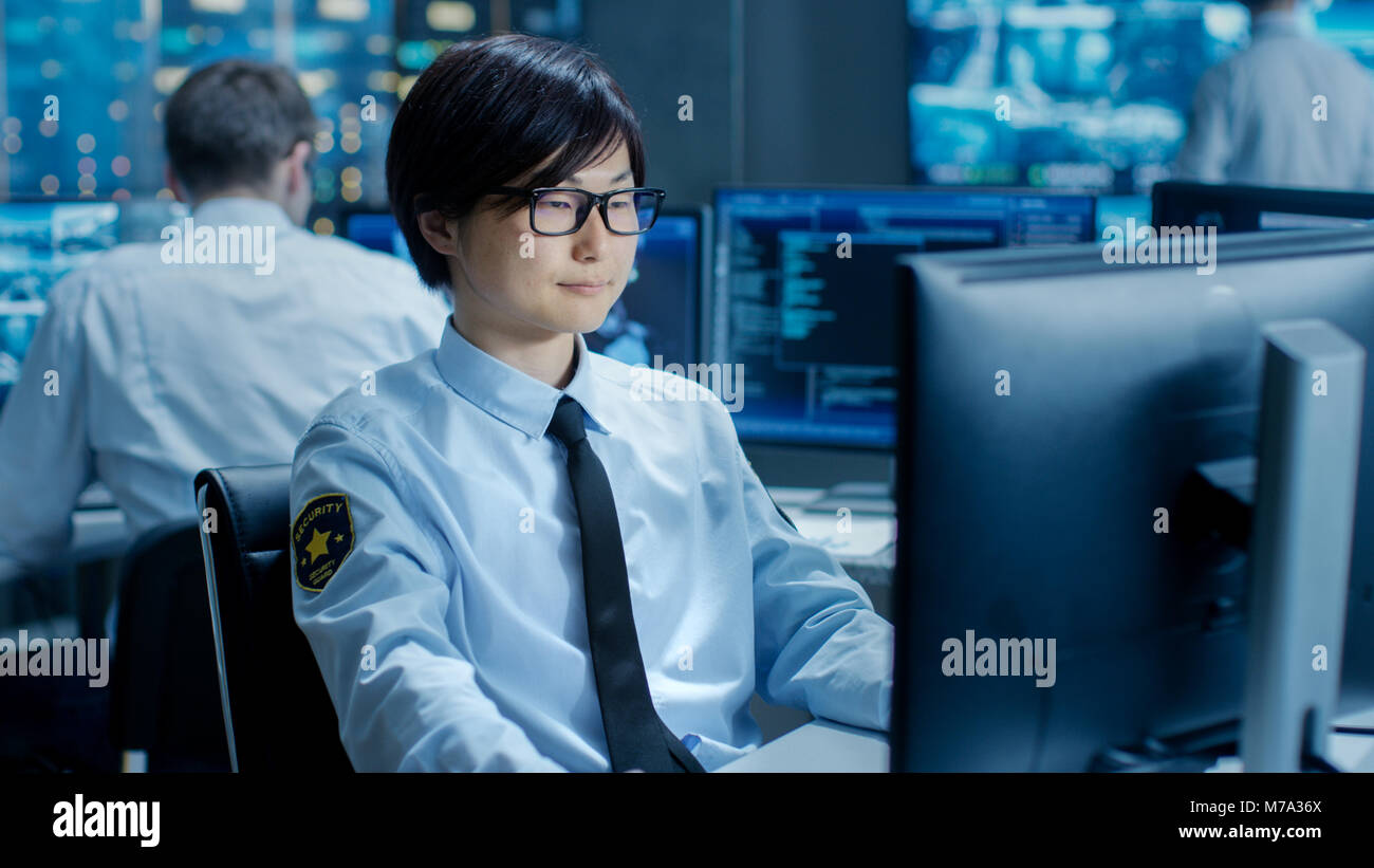 In the Security Command Center Officer at His Workstation Monitors Multiple Screens for Unlawful Infiltration. They're - Stock Image