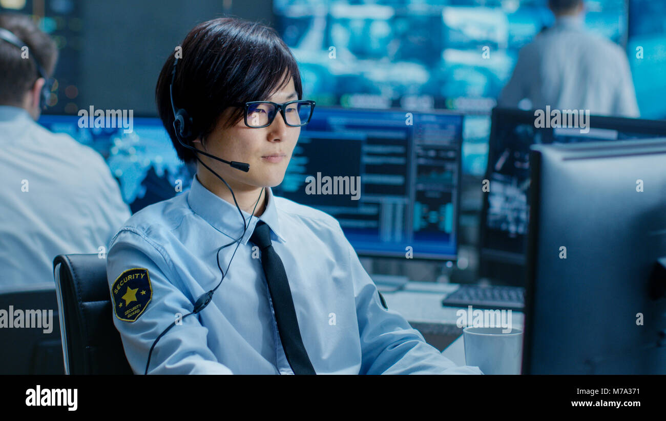 In the Security Command Center Officer at His Workstation Monitors Screens and Communicates with Patrols through - Stock Image