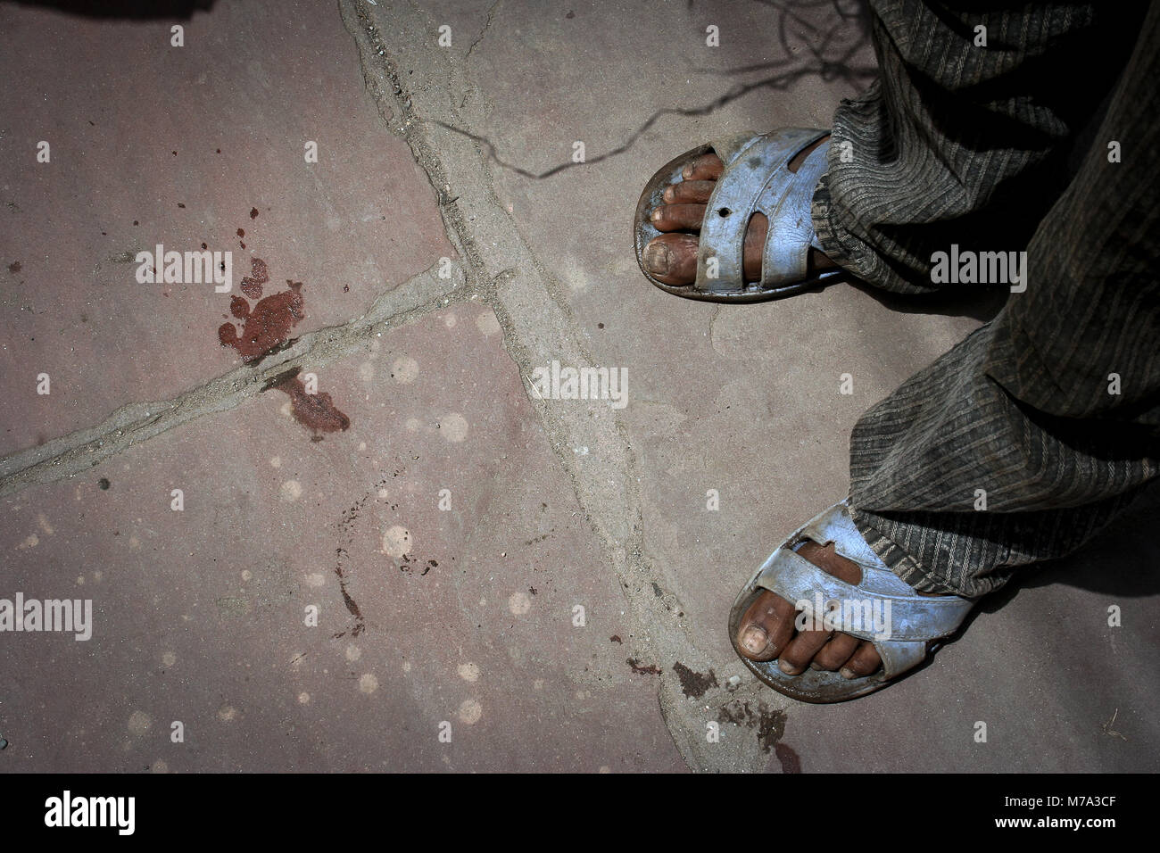 New Delhi, India:The imprint of a foot without shoes is opposed to the feet of a child who wears old sandals. - Stock Image