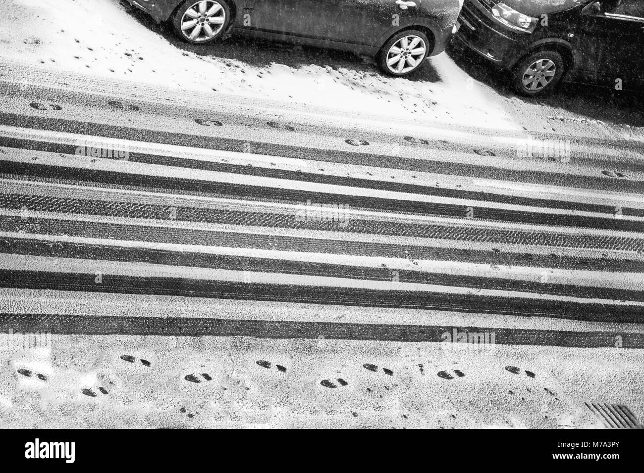 black and white car treads forming stripes on a road and footprints in snow with part of a car parked by the road - Stock Image