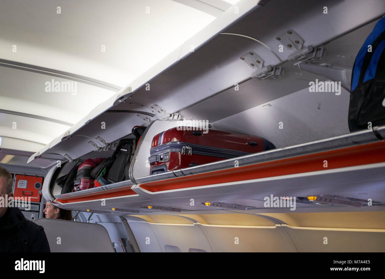 luggage in overhead locker on a flight in the uk - Stock Image