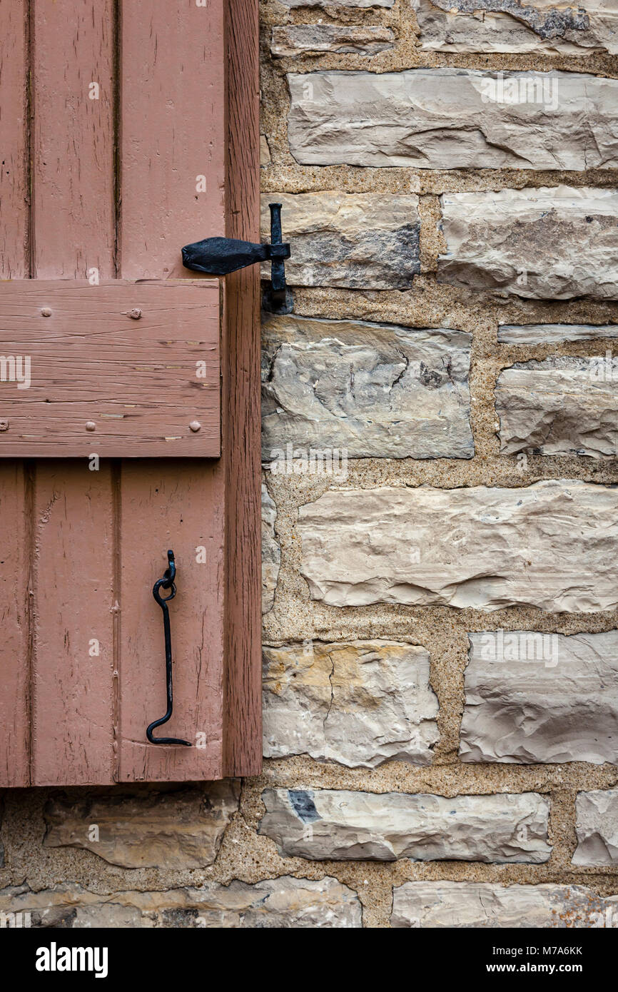Old Stone Wall With Painted Shutter And Steel Hardware Stock