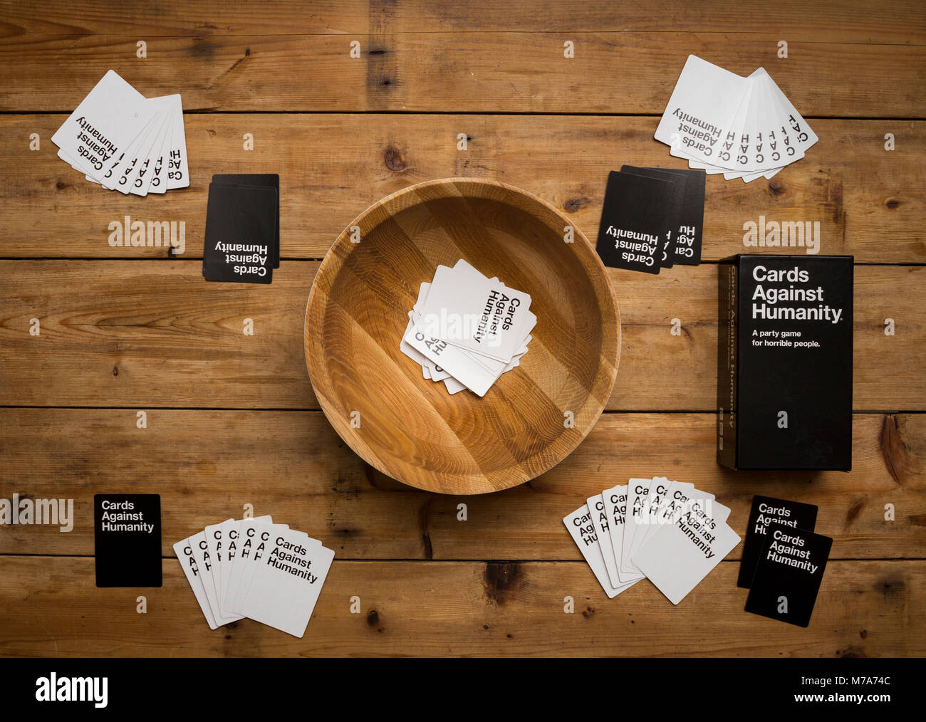 Cards Against Humanity, A party game for horrible people, displayed on a wooden table - Stock Image
