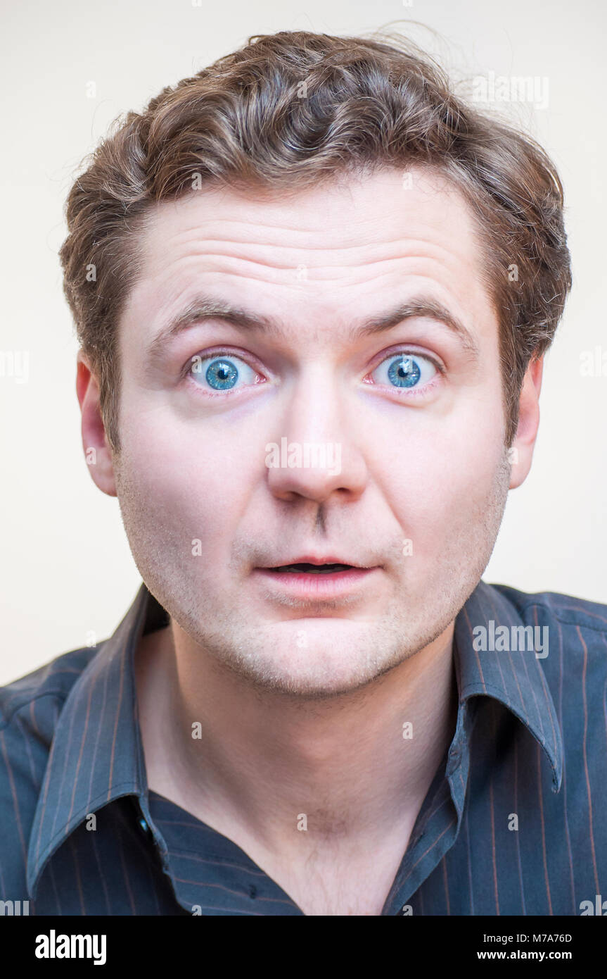 Portrait of young surprised shocked emotional big eyes man with open mouth on white background. - Stock Image
