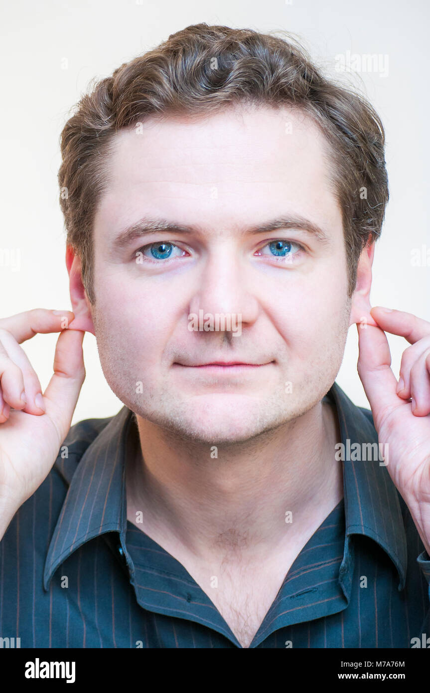 Portrait of young Caucasian Ethnicity blue-eyed man points on his ears on white background. Human face parts. - Stock Image