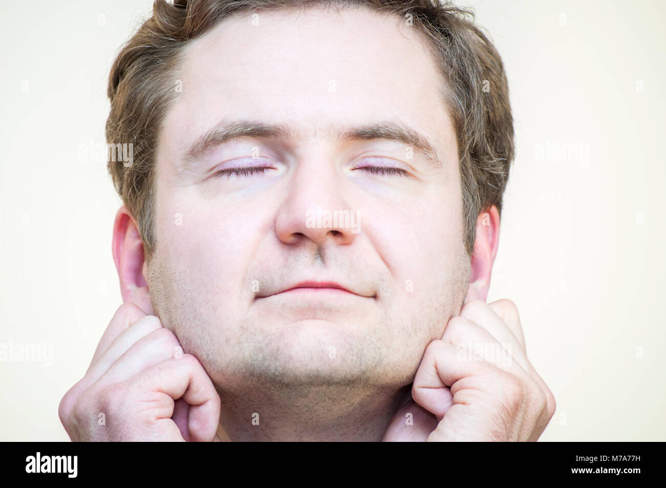 Portrait of young Caucasian Ethnicity tranquil meditating man holding his earlobes on white background. - Stock Image