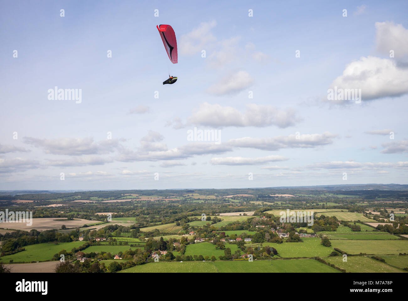 Paraglider flying above the north facing escarpment slope on Harting Down, West Sussex, UK. South Downs National - Stock Image