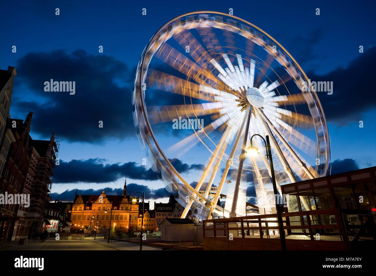 Rotating Ferris wheel located in the Old Town of Gdansk, Poland at night. Green Gate in the background - Stock Image