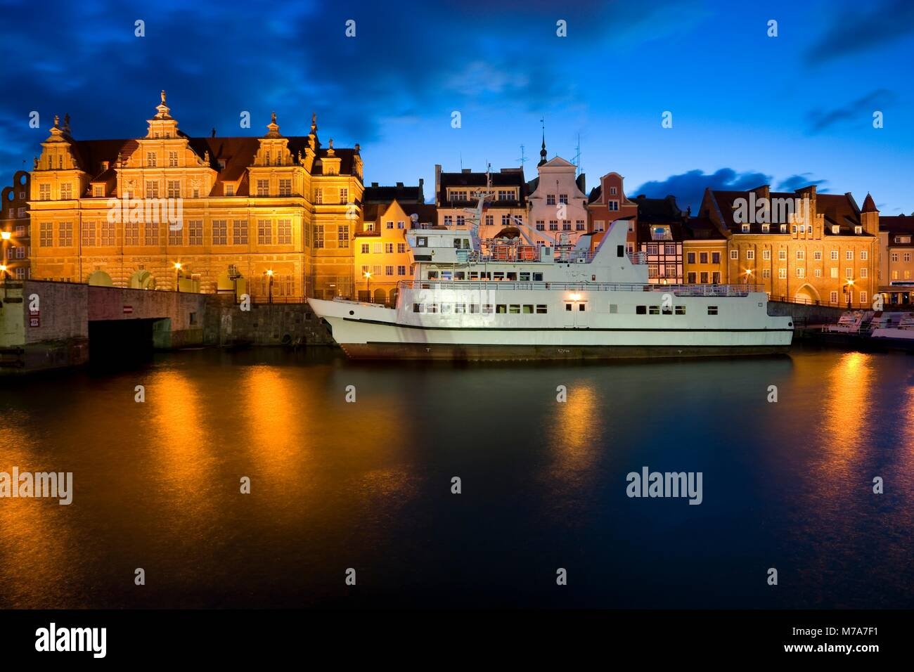Ship moored by Long Embankment on Motlawa River in the Old Town of Gdansk, Poland at night. Illuminated Green Gate - Stock Image