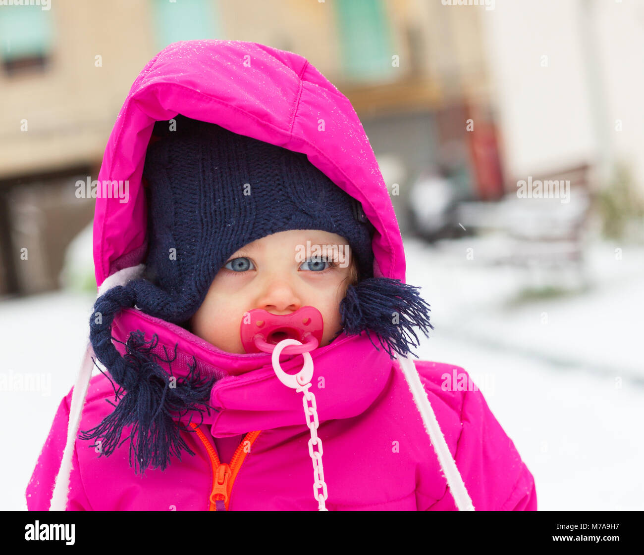 Adorable toddler baby girl in a magenta snow suit playing on the snow. - Stock Image