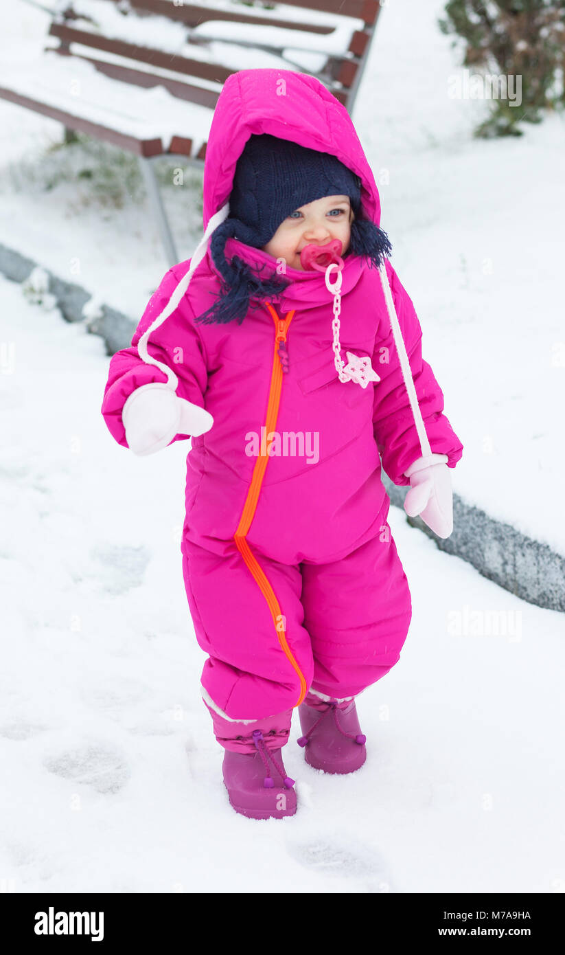7f196f98b766 Adorable toddler baby girl in a magenta snow suit playing on the ...