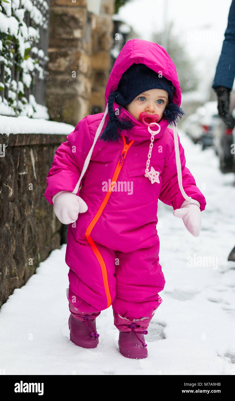 e4350cc64 Adorable toddler baby girl in a magenta snow suit playing on the snow. -  Stock
