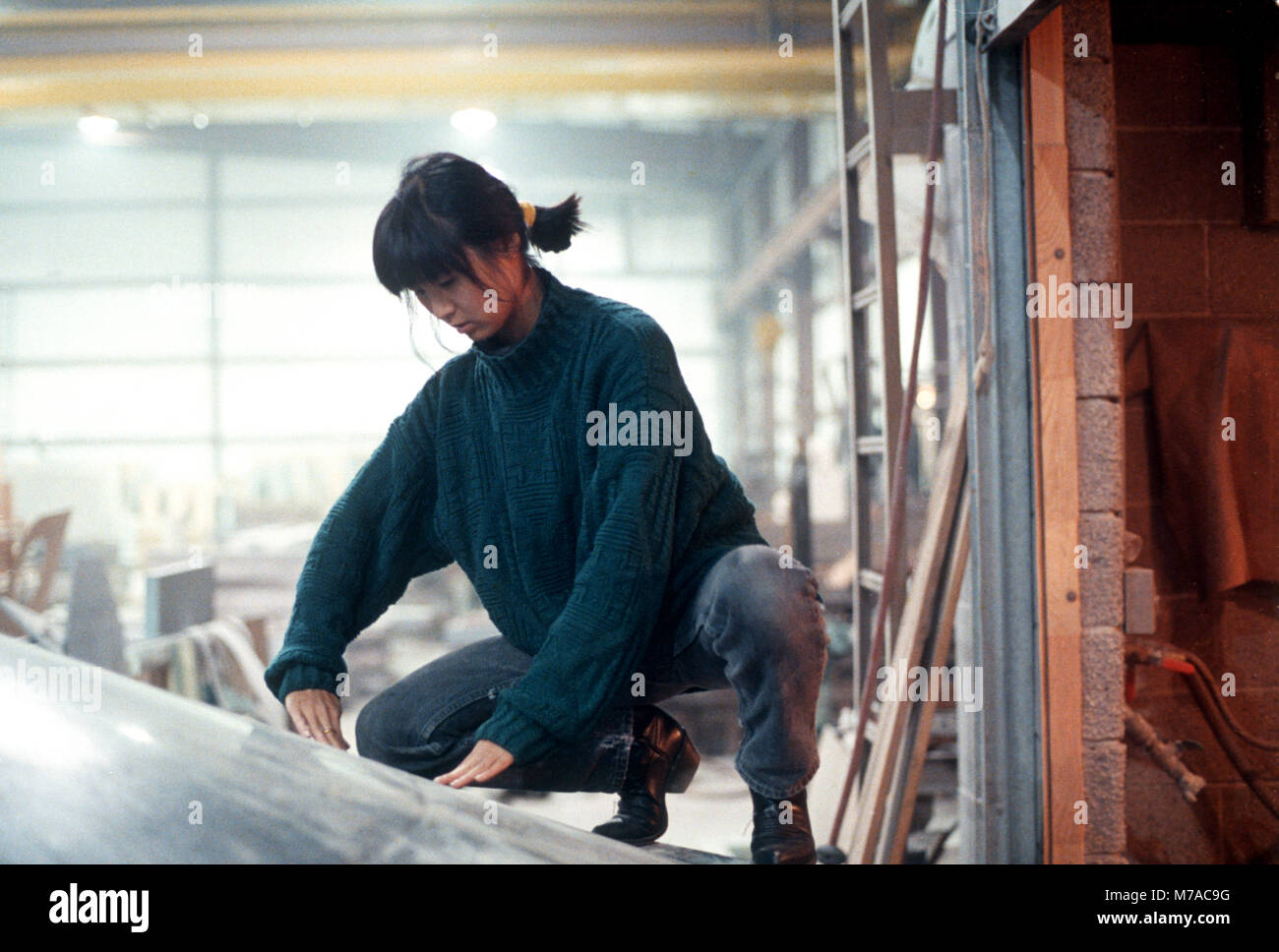 Maya Lin examining inverted water table being fabricated for the Civil Rights Memorial she designed to be installed - Stock Image