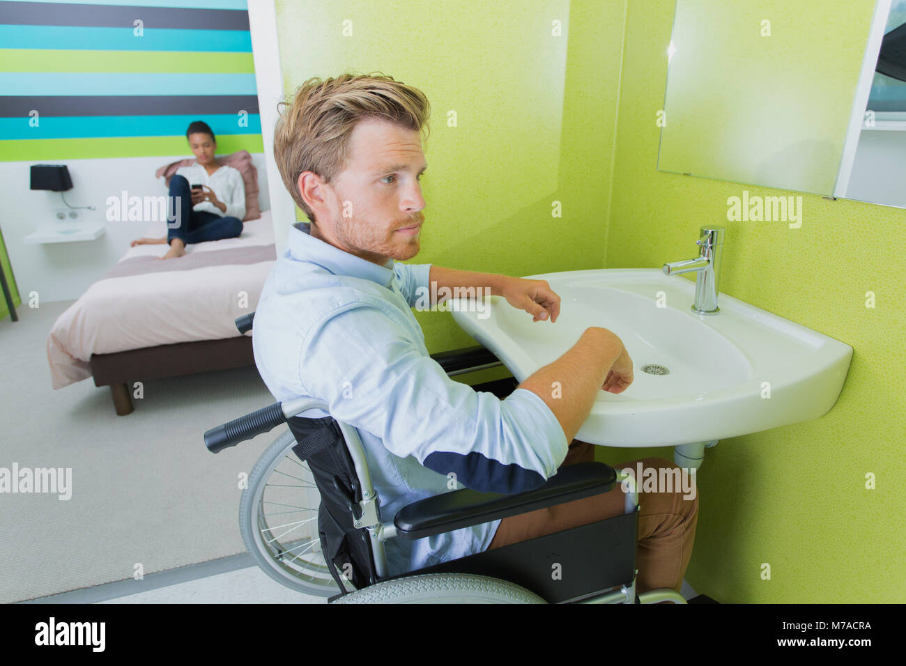 Disabled man using sink in hotel room Stock Photo
