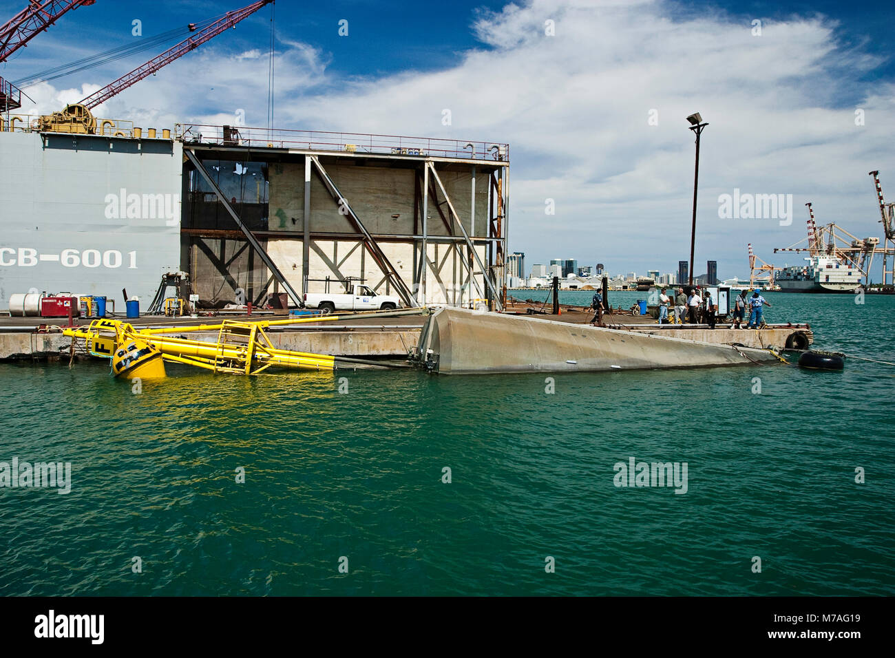 A massive wave energy buoy sits partially submerged in Honolulu Harbor waiting to be towed to Kaneoho Bay, Oahu. - Stock Image