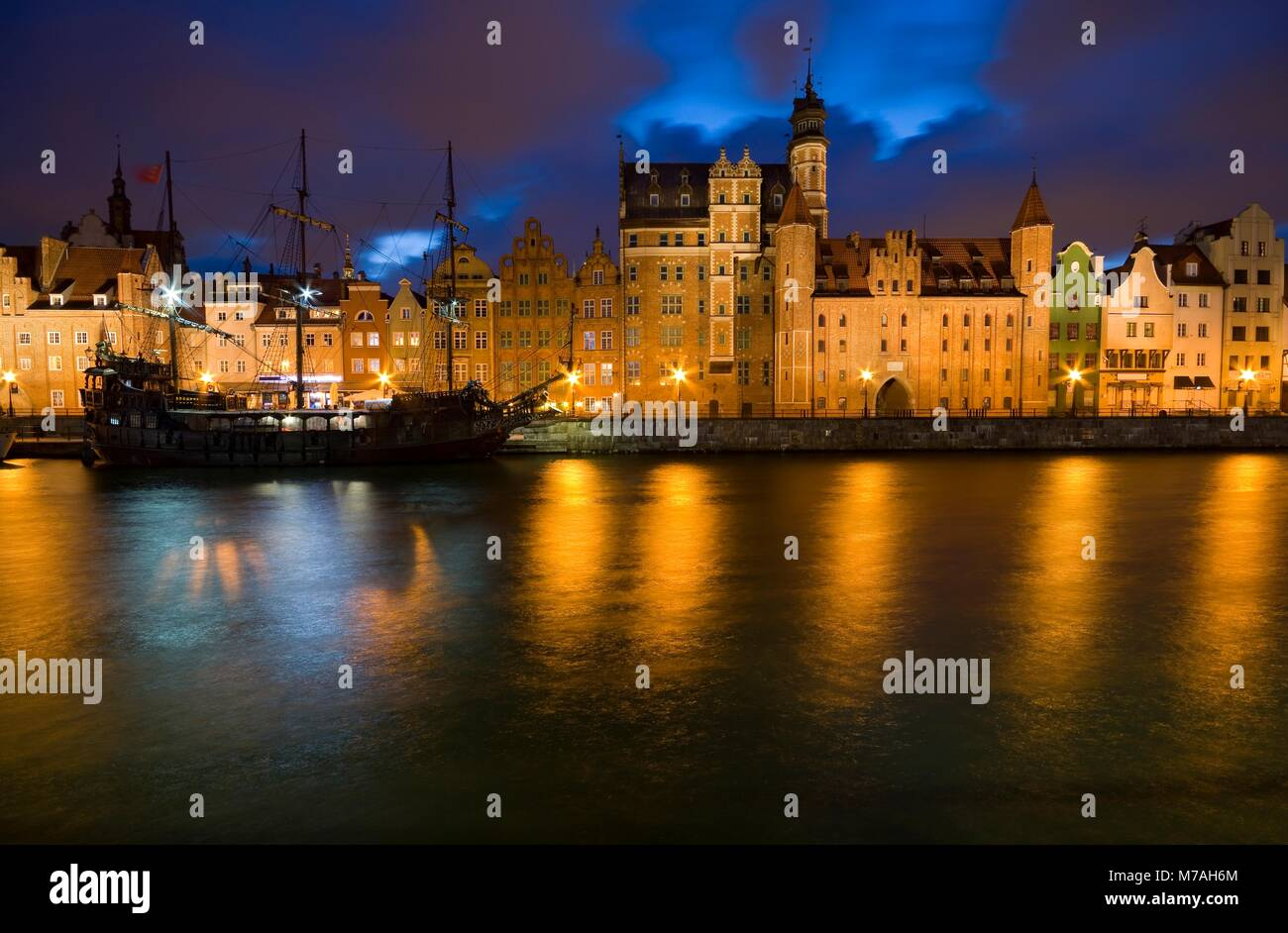Caravel moored by Long Embankment on Motlawa River in the Old Town of Gdansk, Poland at night. Illuminated Mariacka - Stock Image