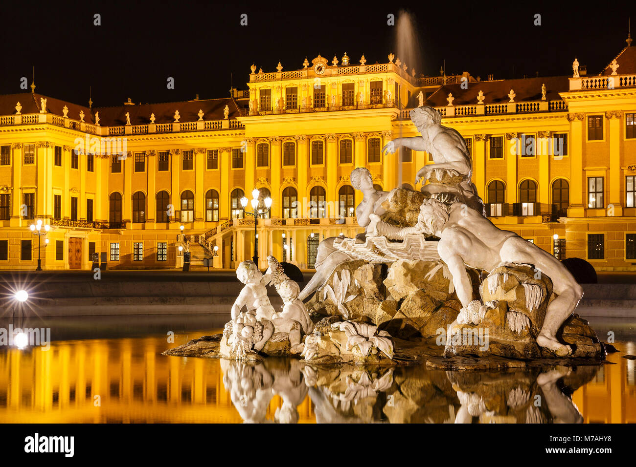 Night photography with reflexion in the fountain on the forecourt of Schönbrunn Palace in Vienna Stock Photo