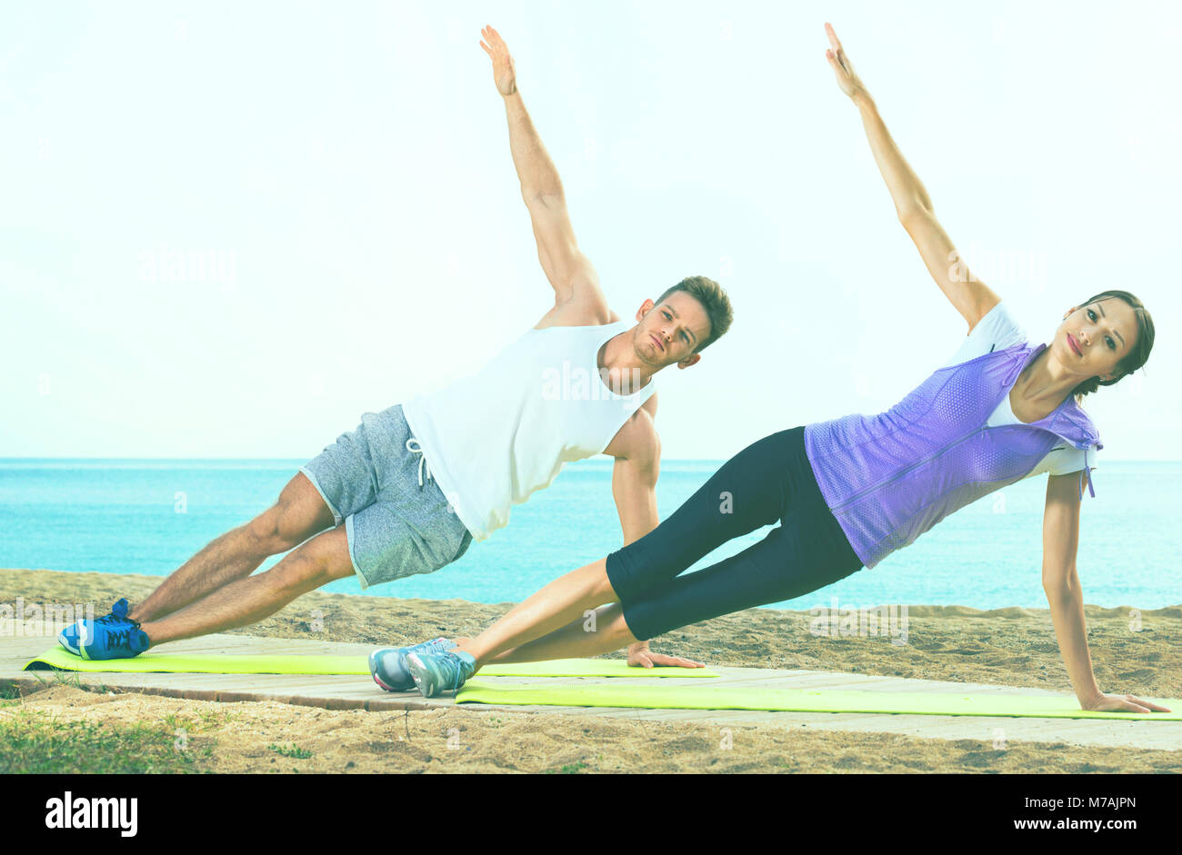 Smiling Couple Training Yoga Poses Sitting On Beach Sunny Morning