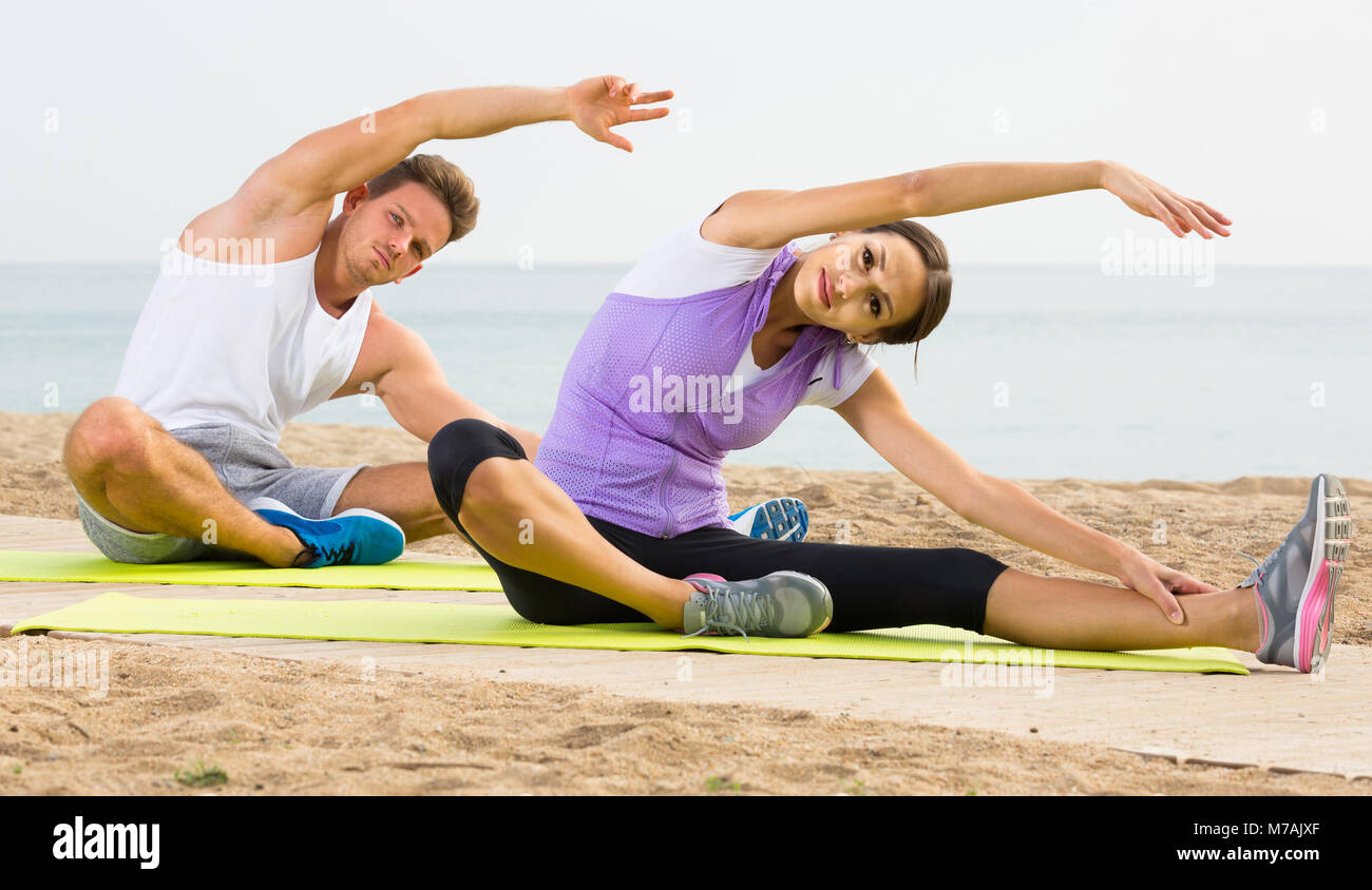 Young Spanish Guy And Girl Practising Yoga Poses Sitting On Beach By Stock Photo Alamy
