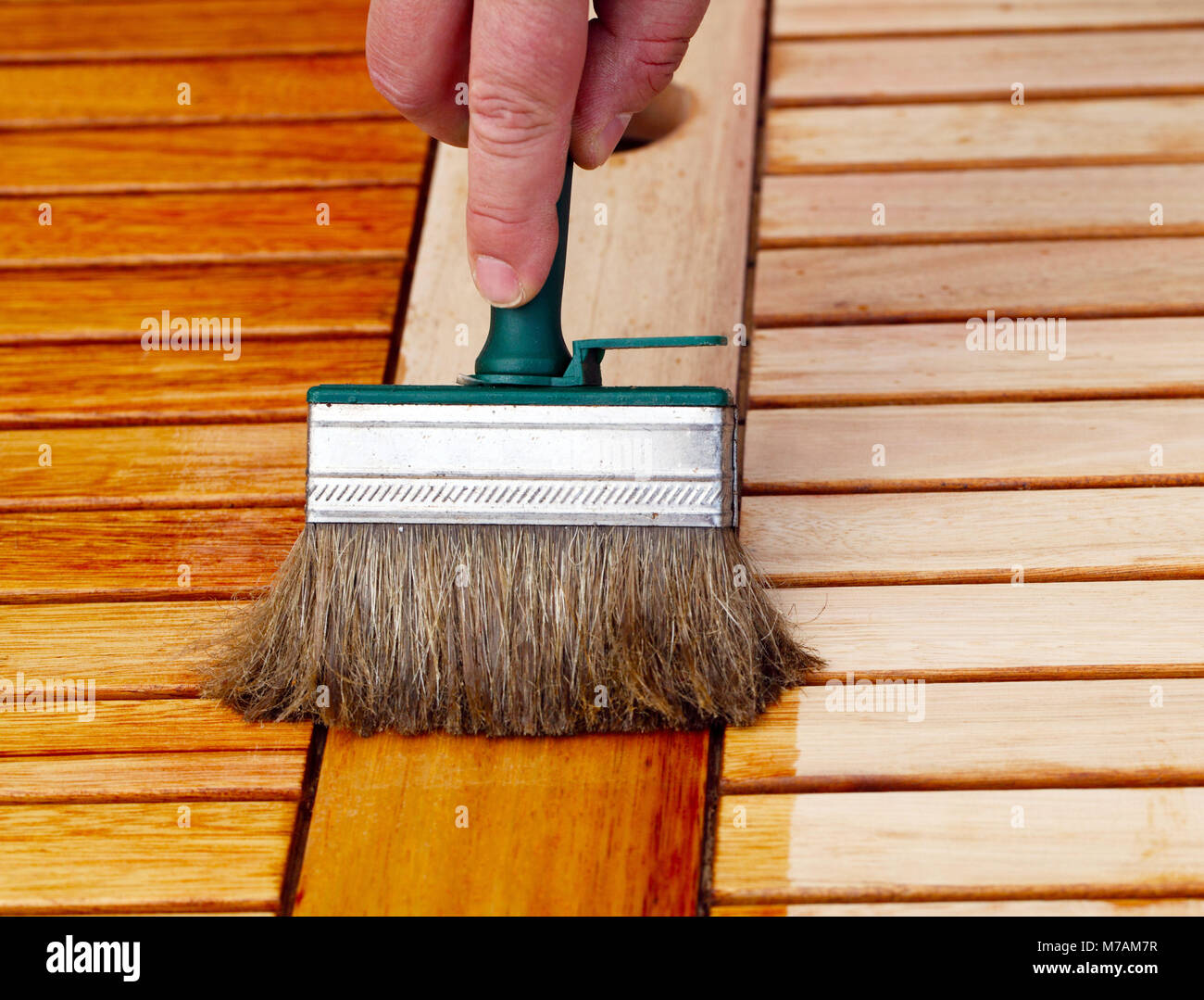 Applying polish to wooden table - Stock Image