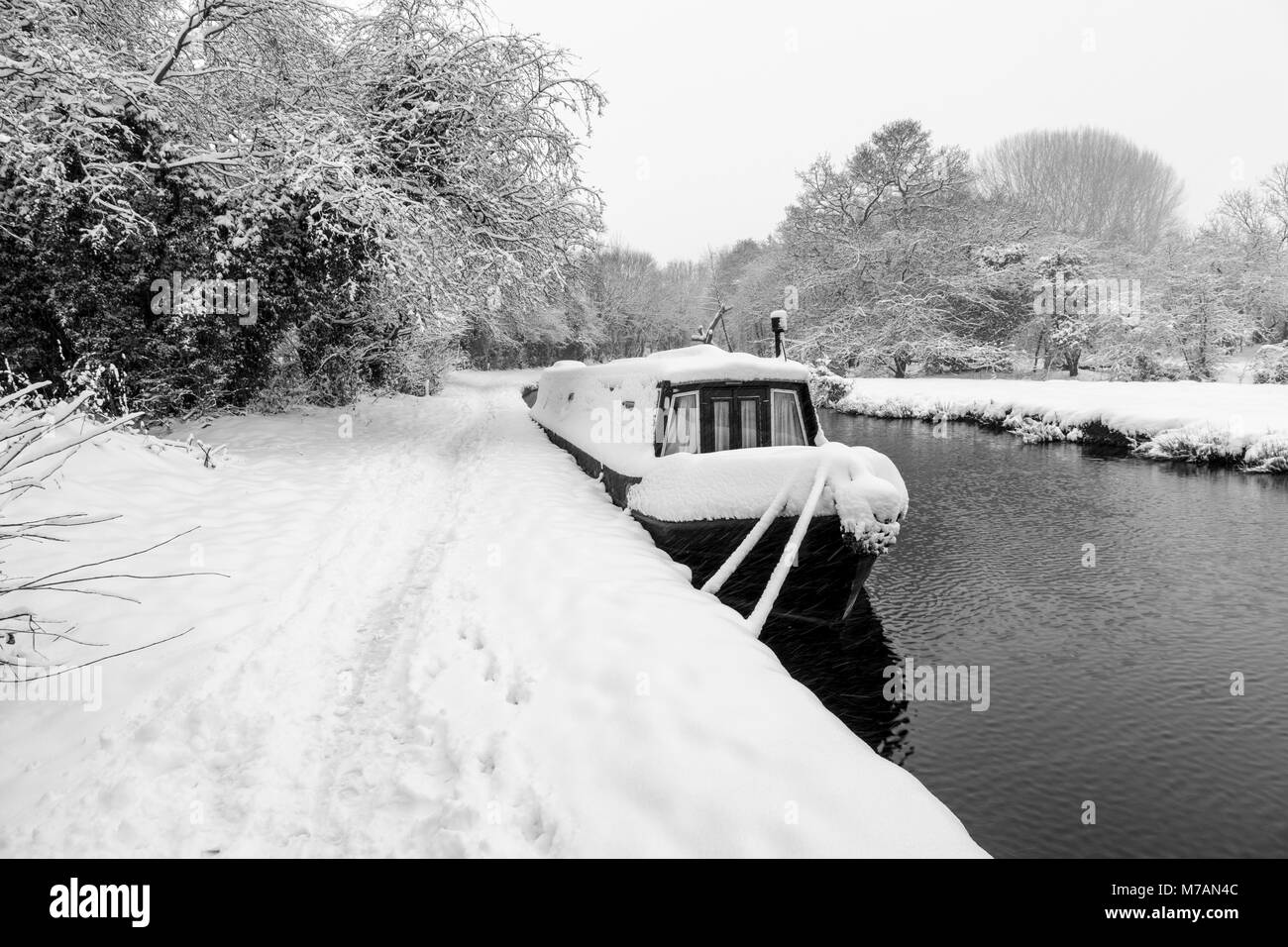 A Narrowboat covered in snow can be seen moored up on the Llangollen Canal - Stock Image