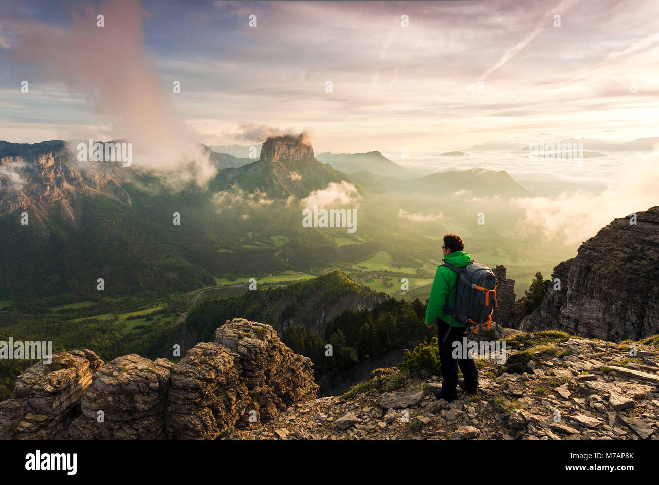 Hiker with far sight on sunrise over Mont Aiguille, Dauphine, France - Stock Image