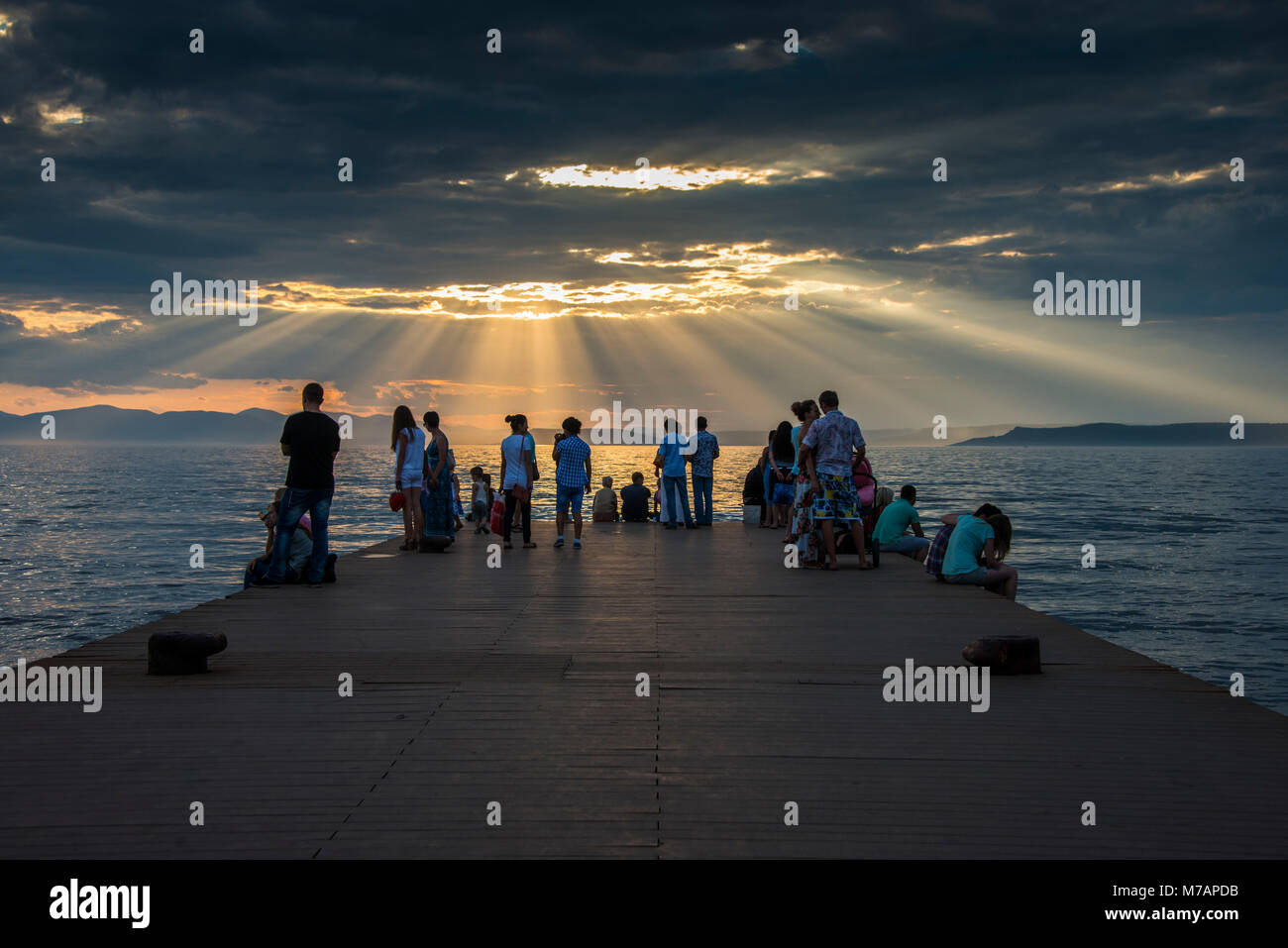 Tourists watching the sun breaking through the clouds above the Amur in  Vladivostok, Russia - Stock Image