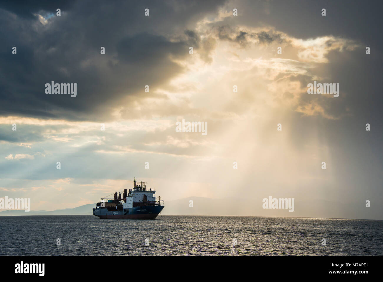 Ship before the Sun breaking through the clouds above the Amur in  Vladivostok, Russia - Stock Image