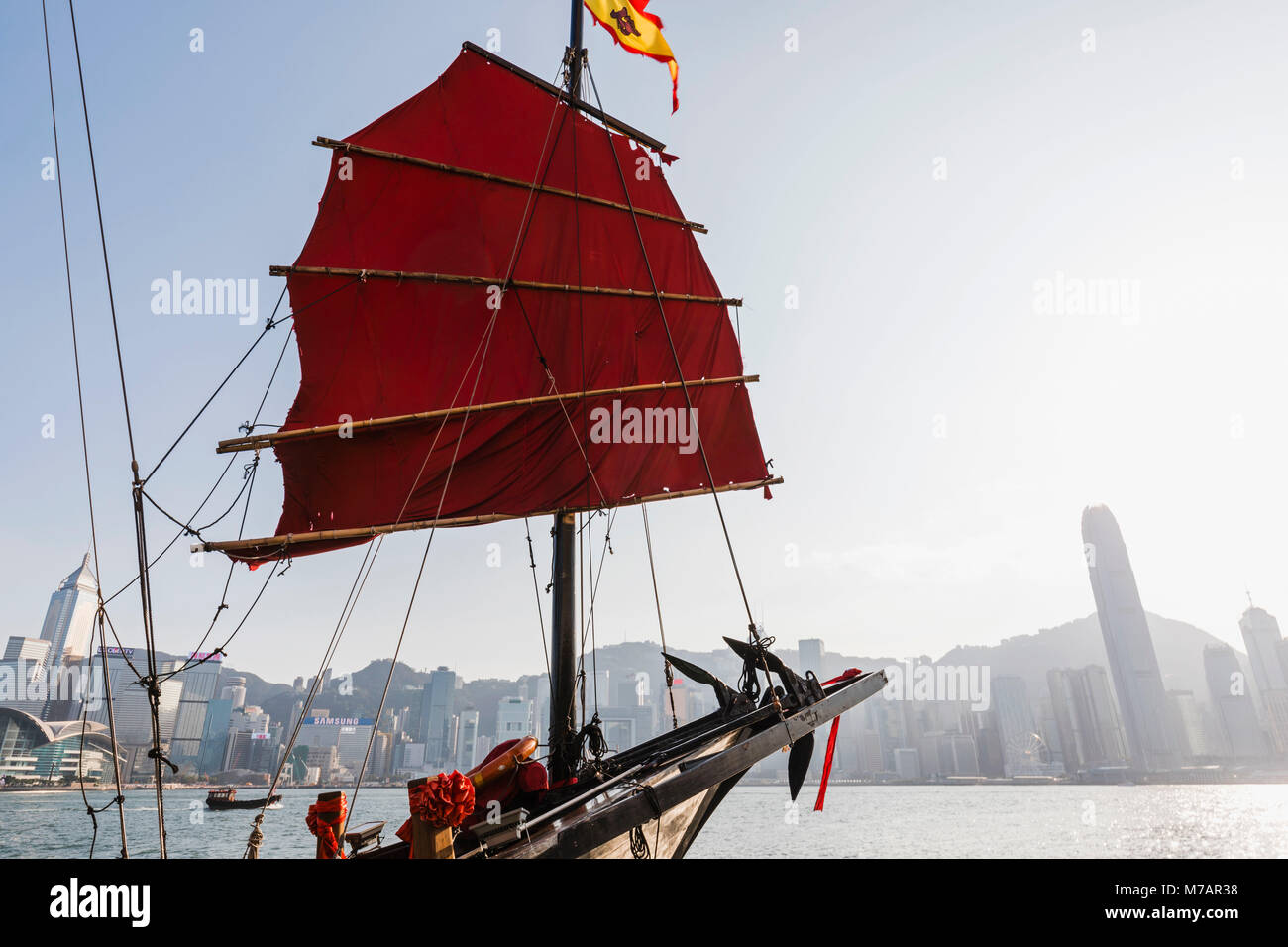 China, Hong Kong, Junk and City Skyline - Stock Image