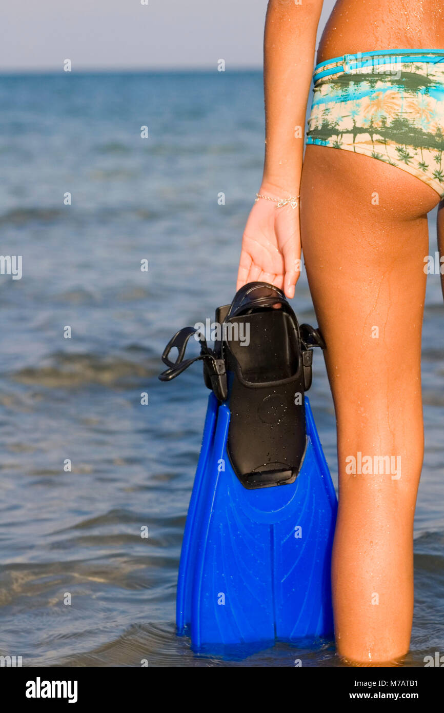 Mid section view of a girl standing in the sea and holding flippers - Stock Image