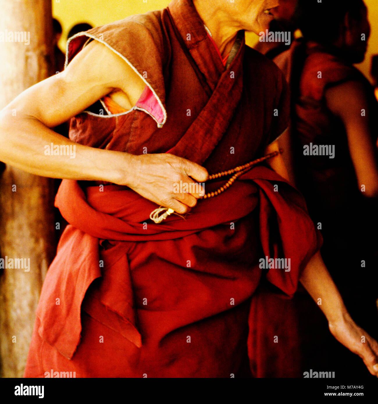 Mid section view of a monk holding prayer beads, Shigatse, Tibet, China - Stock Image