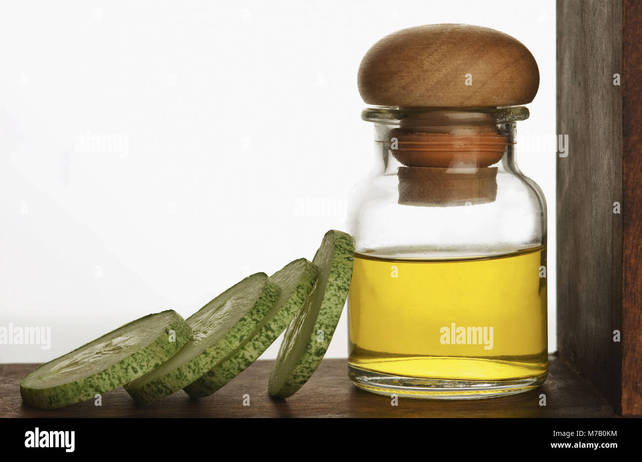 Close-up of therapeutic oil with cucumber slices - Stock Image