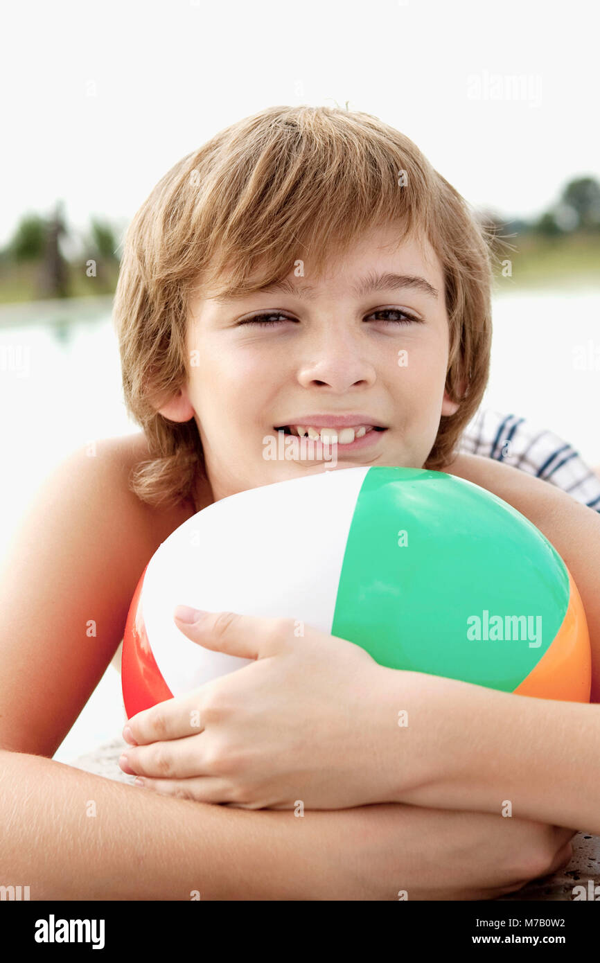 Portrait of a boy holding a beach ball - Stock Image
