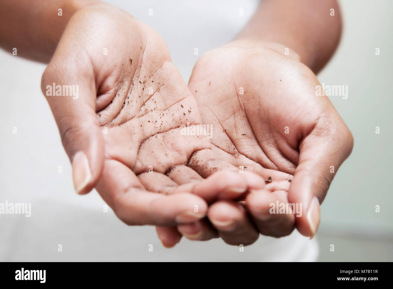 Mid section view of a woman showing her dirty hands - Stock Image