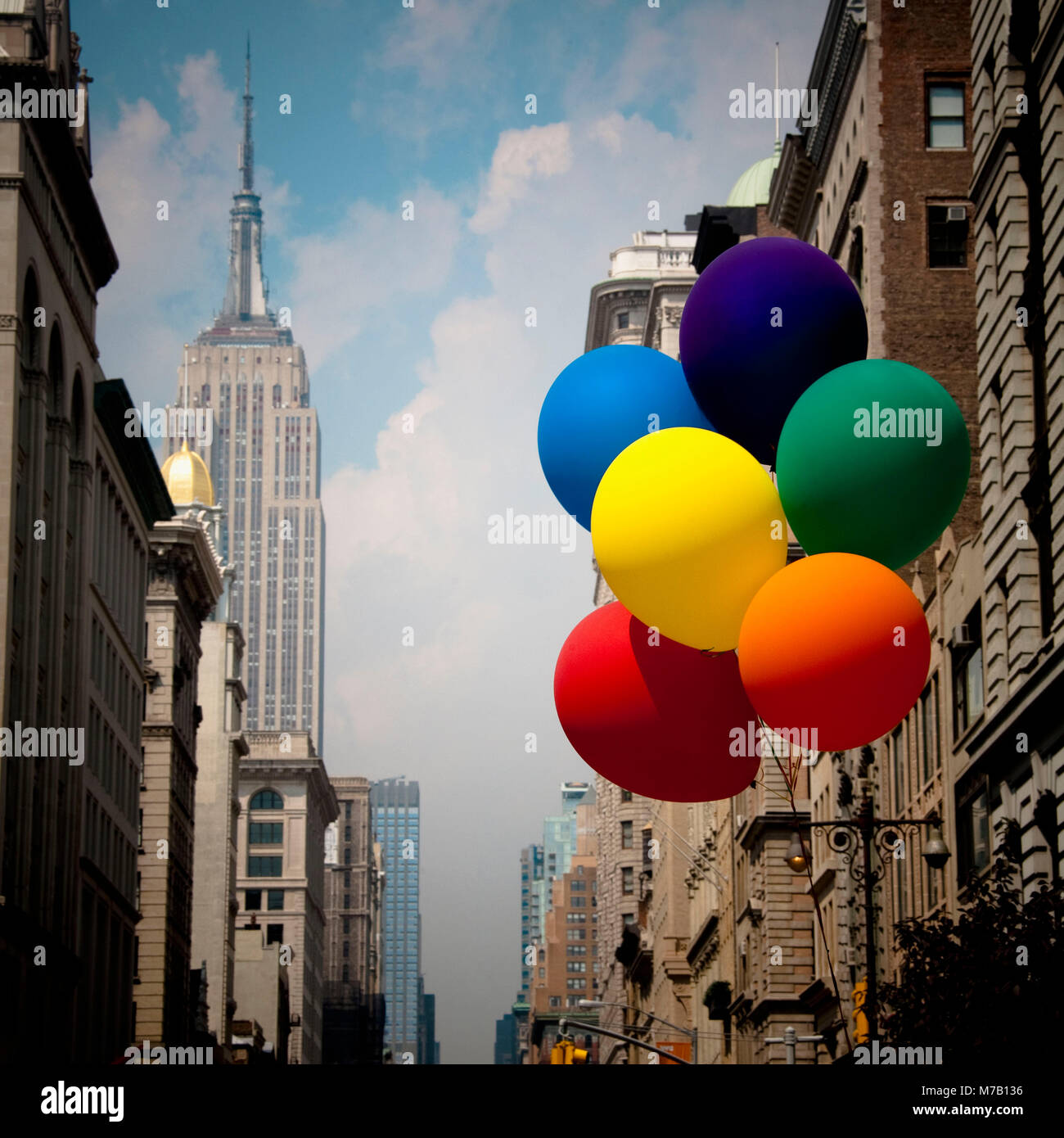 Rainbow color balloons in front of buildings, Empire State Building, New York City, New York State, USA - Stock Image